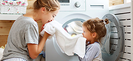 mother with child smelling fresh laundry